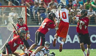 Ryder Bohlander (34) and Dan Burns (4) of the Maryland Terrapins defend against Chris Bocklet (10) of the Virginia Cavaliers during the NCAA Division I lacrosse championship in Baltimore on Monday, May 30, 2011. (Rod Lamkey Jr./The Washington Times)