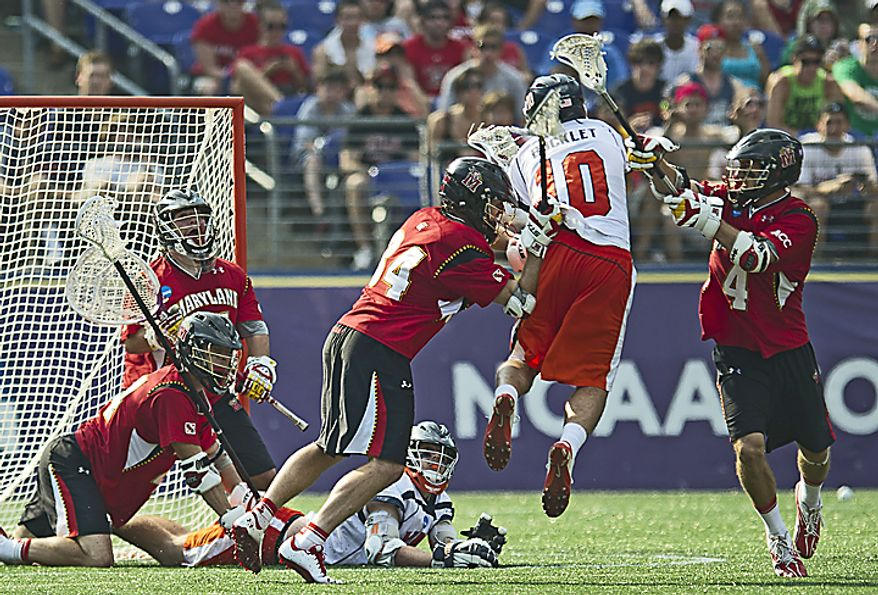 Ryder Bohlander (34) and Dan Burns (4) of the Maryland Terrapins defend against Chris Bocklet (10) of the Virginia Cavaliers as he attempts to score in the third quarter, during the 2011 NCAA Lacrosse Championship at M & T Bank Stadium in Baltimore, Md., Monday, May 30, 2011. The Virginia Cavaliers defeated the Maryland Terrapins 9-7. (Rod Lamkey Jr./The Washington Times)