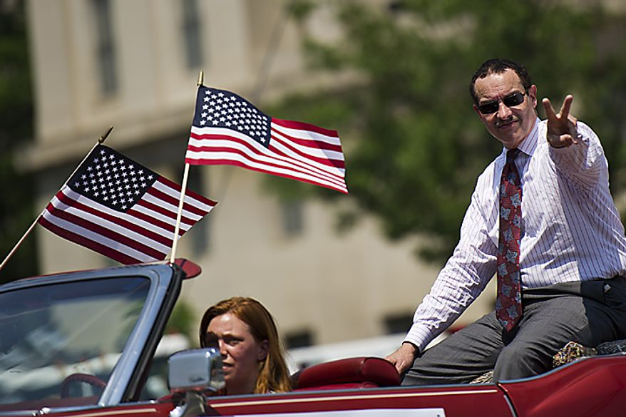 D.C. Mayor Vincent Gray gestures to the crowd as he cruises down Constitution Avenue during the National Memorial Day Parade, in Washington, D.C., Monday, May 30, 2011. (Drew Angerer/The Washington Times)