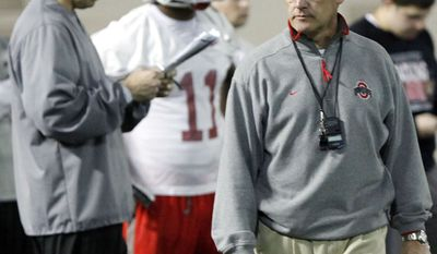 ** FILE ** Ohio State head coach Jim Tressel (right) walks away as assistant head coach Luke Fickell (left) looks over a list of plays during the first day of spring college football practice in Columbus, Ohio, on March 31, 2011. (AP Photo/Terry Gilliam, File)