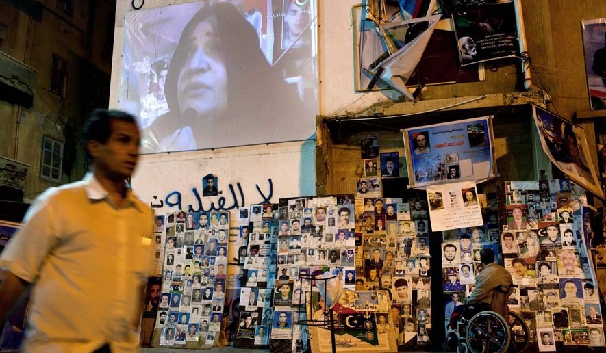 "ASSOCIATED PRESS PHOTOGRAPHS A promotion for the new Libya Alhurra, or ""Free Libya,"" satellite TV station appears on a large screen in Benghazi, the rebel stronghold. The station provides a means for the rebels trying to wrest control from the country from Col. Moammar Gadhafi (shown) to get their message out to the public."
