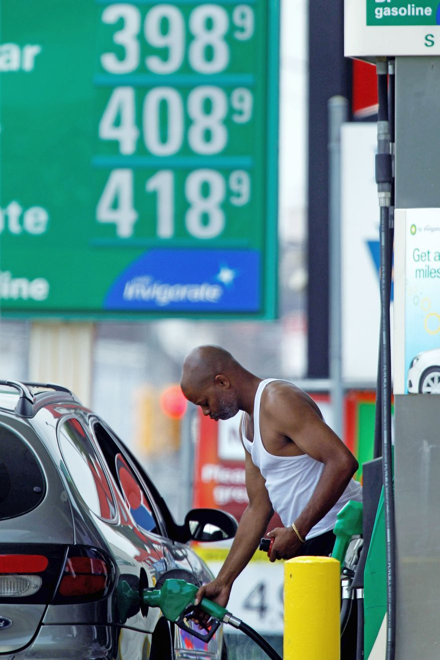 A customer fuels up his car in view of gas prices on Friday in Philadelphia. A survey shows consumers are losing faith that the economy will keep improving. Factors include high gas prices and a moribund housing market. (Associated Press)