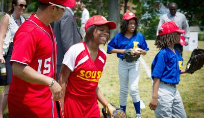 Washington Nationals player Jerry Hairston, Jr., (left) walks with Monea Grier, 13, after having a catch during the Washington Nationals Youth Baseball Academy groundbreaking ceremony Tuesday at Fort DuPont Park in Southeast. (Rod Lamkey Jr./The Washington Times)