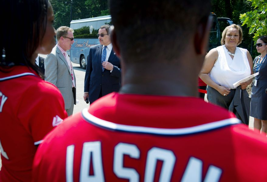 D.C. Mayor Vincent C. Gray (dark suit) chats with Gregory McCarthy, Washington Nationals vice president for government and municipal affairs, as D.C. Council member Yvette Alexander (top, right), of Ward 7, awaits the Nationals Youth Baseball Academy groundbreaking ceremony Tuesday at Fort DuPont Park in Southeast. (Rod Lamkey Jr./The Washington Times)