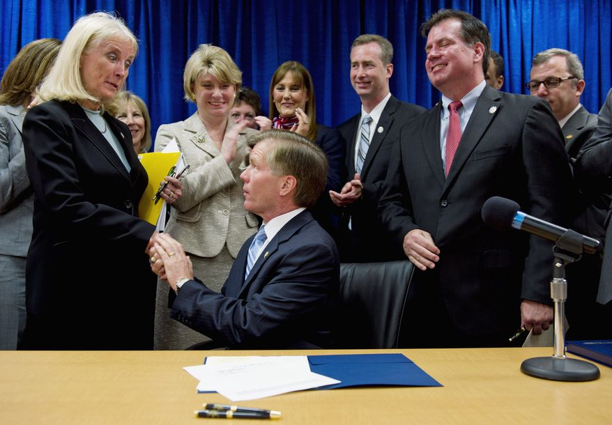 Virginia Gov. Robert F. McDonnell shakes hands with Delegate Vivian E. Watts, Annandale Democrat, after signing sex trafficking legislation into law on Tuesday. (Barbara L. Salisbury/The Washington Times)