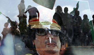 ASSOCIATED PRESS Col. Moammar Gadhafi's portrait hangs behind a window that reflects people from several African countries gathering this week at the dictator's Bab al-Aziziya compound, a regular target of NATO airstrikes in Tripoli, Libya.