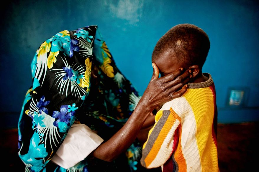 A mass rape victim comforts her son in the town of Fizi, Congo. (Washington Times File)