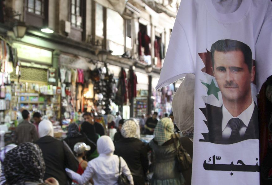 """Syrians walk past a T-shirt with a portrait of Syrian President Bashar Assad with Arabic wording that reads """"we love you"""" at a popular market in downtown Damascus, Syria, on May 30, 2011. (Associated Press)"""
