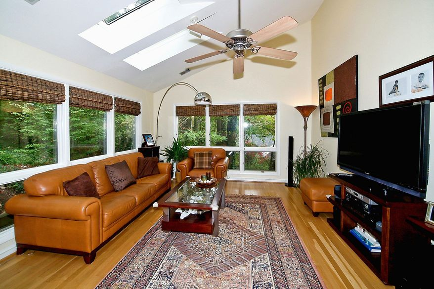 The family room has five skylights, floor-to-ceiling windows on two walls and hardwood flooring.