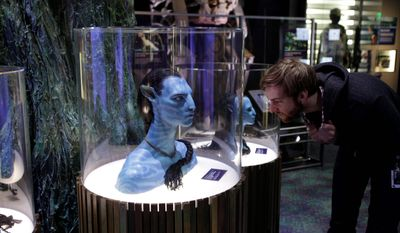 "Benjamin Shown, a graphic designer for the Experience Music Project and Science Fiction Museum in Seattle, checks out a model of ""Avatar"" character Jake Sully's other self. The exhibit draws visitors into the process of creating the film's world. (Associated Press)"