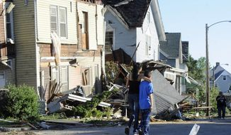 People walk past storm damage a day after a tornado struck in Springfield, Mass., on June 2, 2011. (Associated Press)