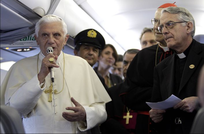 Pope Benedict XVI answers reporters' questions aboard the airplane heading to Zagreb, Croatia, Saturday, June 4, 2011. Pope Benedict XVI will be visiting the Croatian capital from June 4 to 5 for the first time. At right is father Federico Lombardi, Vatican spokesperson and cardinal Tarciso Bertone, Vatican Secretary of State, second from right. (AP Photo/Pier Paolo Cito)