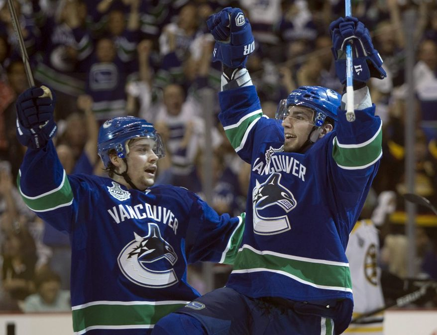 Vancouver Canucks left wing Alex Burrows, right, celebrates with teammate Mason Raymond after scoring the first goal against the Boston Bruins during the first period in Game 2 of the NHL hockey Stanley Cup finals. Burrows also assisted on the second goal and scored the game-winner in overtime as the Canucks won 3-2. (AP Photo/The Canadian Press, Darryl Dyck)