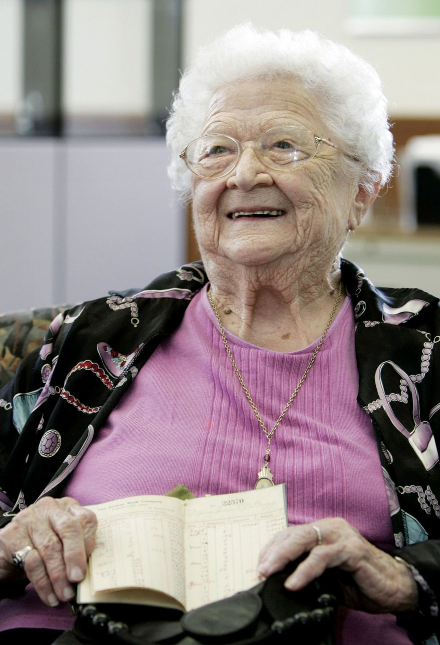 June Gregg of Bainbridge, Ohio, displays her original bankbook during her 100th-birthday celebration at the Chillicothe branch of Huntington National Bank on Tuesday in Chillicothe, Ohio. Miss Gregg's father opened a bank account for her in 1913, and she has held the same account ever since. (Associated Press)