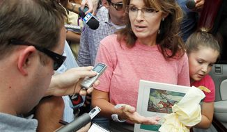 Former Alaska Gov. Sarah Palin, holding a booklet depicting Paul Revere, speaks Thursday with reporters as she tours Boston's North End. (Associated Press)