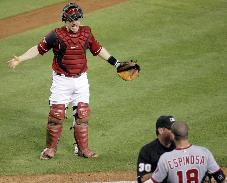 ASSOCIATED PRESS Arizona catcher Miguel Montero (top) exchanges words with Washington second baseman Danny Espinosa, who is restrained by umpire Rob Drake on Sunday after Espinosa was hit by a pitch.