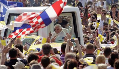 Pope Benedict XVI, aboard his popemobile, waves to the faithful at the Zagreb Hippodrome before celebrating a Mass on the National Day of Croatian Family during the last day of his two-day visit to Croatia on Sunday, June 5, 2011, in Zagreb, Croatia. (AP Photo/Pier Paolo Cito)
