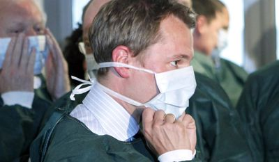 German Health Minister Daniel Bahr dons a mask and gloves during a visit to the University Medical Center in Hamburg-Eppendorf, Germany, on Sunday, June 5, 2011. (AP Photo/dapd, Focke Strangmann)
