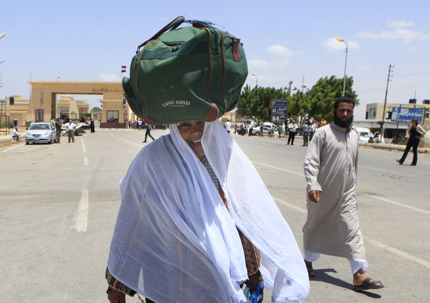 ** FILE ** A Palestinian woman carries her bag atop her head as enters Egypt from the Gaza Strip at the Rafah border crossing (in the background) on Saturday, May 28, 2011. (AP Photo/Amr Nabil)