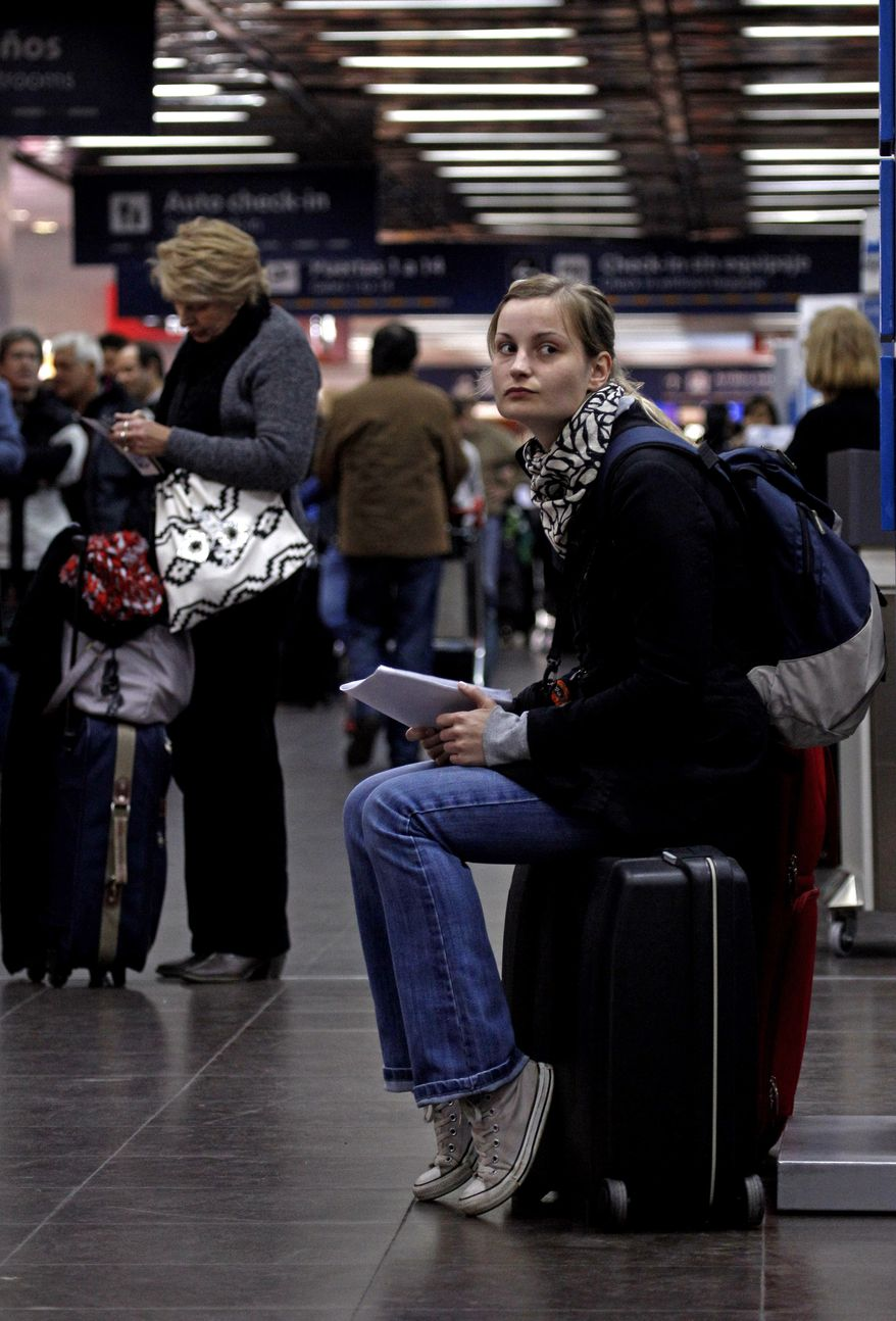 French tourist Juilette, who did not give her surname, sits on her luggage at the Jorge Newbery Airport in Buenos Aires after her flight to Uruguay was canceled because of an ash cloud from Chile's Peyuhue volcano. (AP Photo/Natacha Pisarenko)