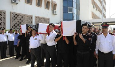 In this photo released by the Syrian official news agency SANA and according to them, Syrian policemen carry the coffins of their comrades who were killed in recent violence in the country, during their funeral procession at the Police Hospital in Damascus, Syria on June 7, 2011. (Associated Press/SANA)