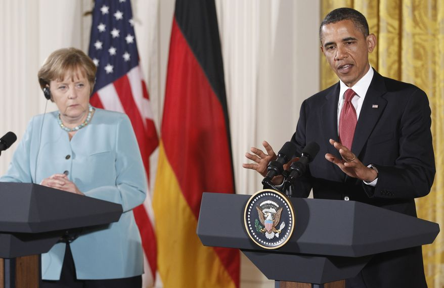 President Barack Obama and German Chancellor Angela Merkel take part in a joint news conference in the East Room at the White House in Washington, Tuesday, June 7, 2011. (AP Photo/Charles Dharapak)