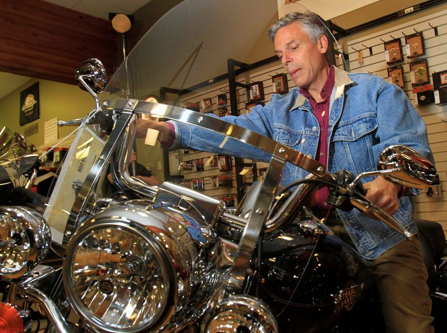 Jon Huntsman Jr. sits on a Harley-Davidson at a dealership during a May visit to Manchester, N.H. The GOP presidential candidate is back in New Hampshire, traversing the campaign trail on a Harley Road King. (Associated Press)