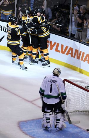 Boston Bruins center Rich Peverley celebrates his goal with teammates as Vancouver Canucks goalie Roberto Luongo looks on during Game 4 of NHL Stanley Cup finals. Peverley had two goals in the Bruins' 4-0 win. The series is now tied 2-2. (