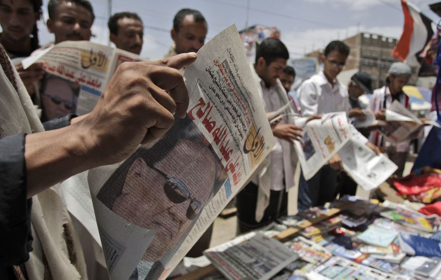 """On Tuesday, June 7, 2011, anti-government protesters in Sanaa, Yemen, read newspapers featuring on the front page a photograph of Vice President Abed Rabbo Mansour Hadi and a headline that translates as """"What's after Ali Abdullah Saleh."""" (AP Photo/Hani Mohammed)"""