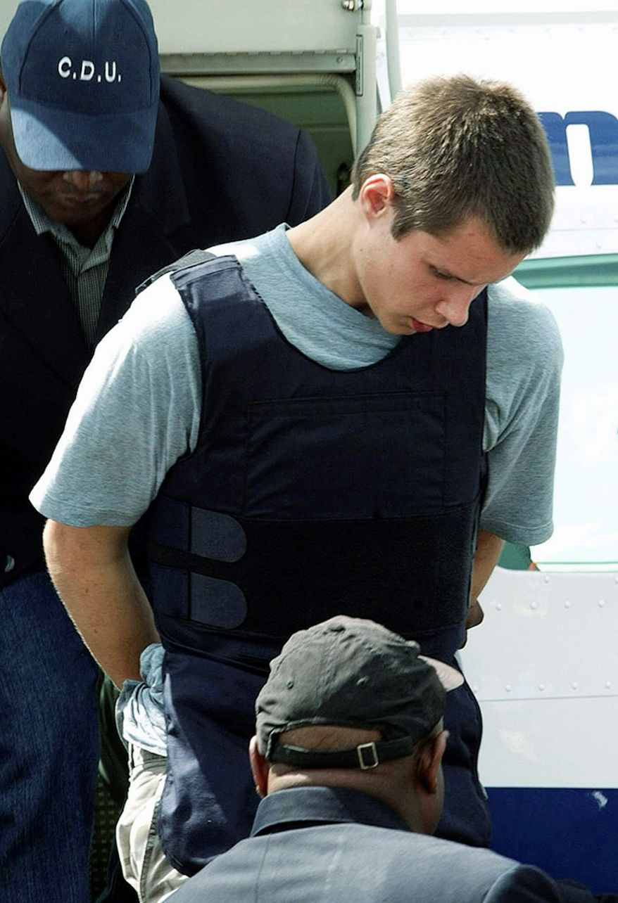 Colton Harris-Moore, seen here in July 2010, exits a plane handcuffed and escorted by police upon arrival in Nassau, Bahamas. He was subsequently extradited back to the U.S. for trial. On Thursday, he pleaded not guilty to a series of crimes. (Associated Press)