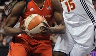 Washington Mystics' Nicky Anosike, left, drives to the basket while guarded by Connecticut Sun's Asjha Jones, right, during the second half of a WNBA basketball game in Uncasville, Conn., on Saturday, June 4, 2011. (AP Photo/Jessica Hill)