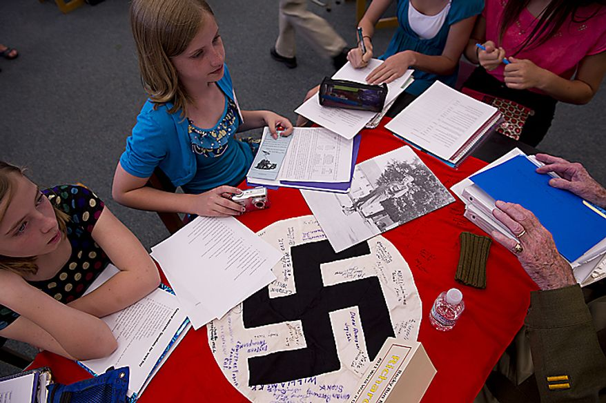 "Rocky Run Middle School seventh-graders Alli Bolton, left, and Stephanie Introne, both 12, listen to a World War II vet's stories, including the one about how he captured this Nazi flag, during the school's 10th annual World War II Day, called ""The Latest Generation Meets the Greatest Generation,"" on Thursday, June 9, 2011. The day included small-group interviews with WWII vets as well as panel discussions and World War II-inspired entertainment provided by the students. More than 100 vets participated. (Barbara L. Salisbury/The Washington Times)"