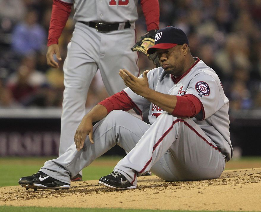 Washington Nationals starting pitcher Livan Hernandez sits on the mound after being knocked down while catching a line drive hit by San Diego Padres' Chris Denorfia in the third inning of a baseball game, Thursday, June 9, 2011 in San Diego. (AP Photo/Lenny Ignelzi)