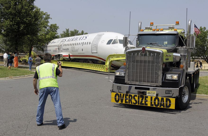 A worker with J. Supor & Son Trucking & Rigging Co. guides the flatbed truck carrying the fuselage of US Airways flight 1549 as it arrives in Charlotte, N.C., on June 10, 2011. The plane that made a miraculous landing on the Hudson River two years ago will be displayed in a museum in Charlotte. (Associated Press)