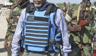 ** FILE ** In this file photo dated Wednesday, Feb. 23, 2011, Somali's Interior Minister Abdishakur Sheik Hassan, centre, is escorted by Somali soldiers in Mogadishu, Somalia. (AP Photo/Mohamed Sheikh Nor)