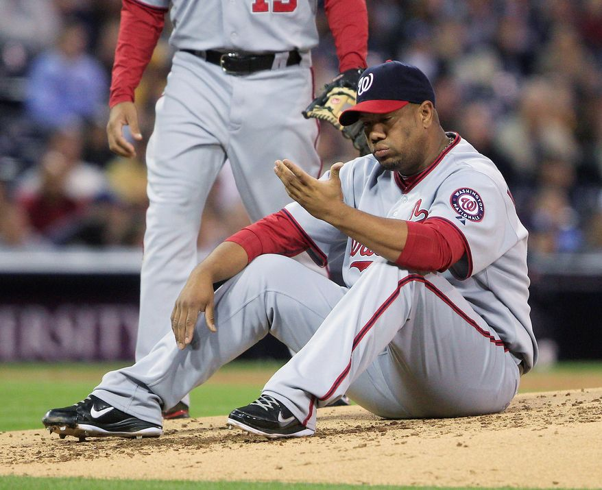 Nationals pitcher Livan Hernandez sits on the mound after being knocked down by a line drive that shot into his glove in a loss Thursday in San Diego. The righthander's ties to a drug dealer in Puerto Rico are under investigation. (Associated Press)
