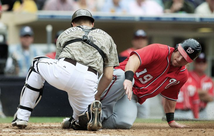 ASSOCIATED PRESS San Diego catcher Nick Hundley blocks the plate as he tags out Washington outfielder Laynce Nix, who was trying to score from third on an infield grounder in the eig