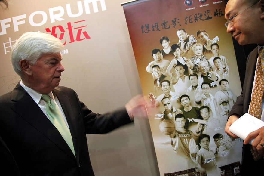 ASSOCIATED PRESS Chris Dodd (left) looks at a Chinese poster about anti-piracy prior to a seminar as part of the 14th Shanghai International Film Festival. Mr. Dodd heads the Motion Picture Association of America.