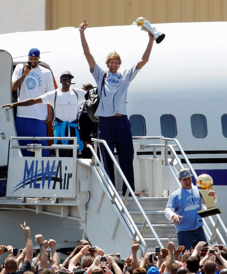 Dallas Mavericks' Dirk Nowitzki, center, of Germany, raises his MVP trophy followed by teammates Jason Terry, second from left, and Tyson Chandler, left, as they exit the charter with owner Mark Cuban carrying the NBA Championship basketball trophy after the team's arrival at Love Field in Dallas, Monday, June 13, 2011. The Mavericks beat the Heat to win the NBA championship. (AP Photo/LM Otero)