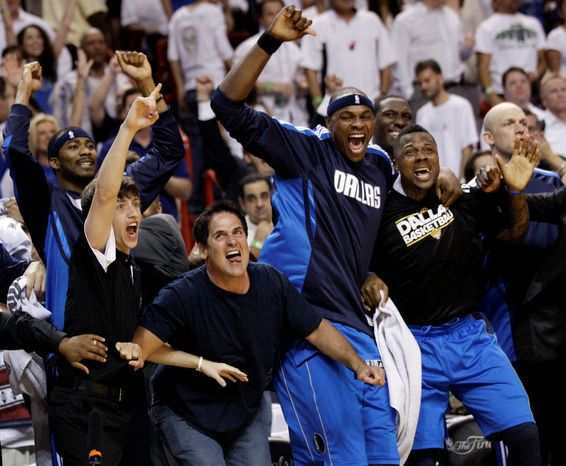 Dallas Mavericks owner Mark Cuban celebrates with Brendan Haywood and DeShawn Stevenson, right, in the final seconds of the second half of Game 6 of the NBA Finals basketball game against the Miami Heat Sunday, June 12, 2011, in Miami. The Mavericks won 105-95 to win the series. (AP Photo/David J. Phillip)