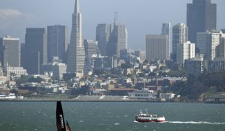 An Oracle Racing AC45, skippered by James Spithill, makes its way past a cruise boat and the San Francisco skyline in this view from Sausalito, Calif., Monday, June 13, 2011. (AP Photo/Eric Risberg)