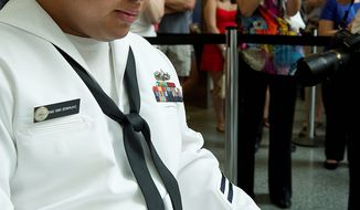 Barbara L. Salisbury/The Washington Times Petty Officer 2nd Class Hanlin Edwin, from Micronesia but now living in the District, examines his new certificate of naturalization, as an onlooker applauds, after he and 19 others became naturalized U.S. citizens Tuesday in Washington.