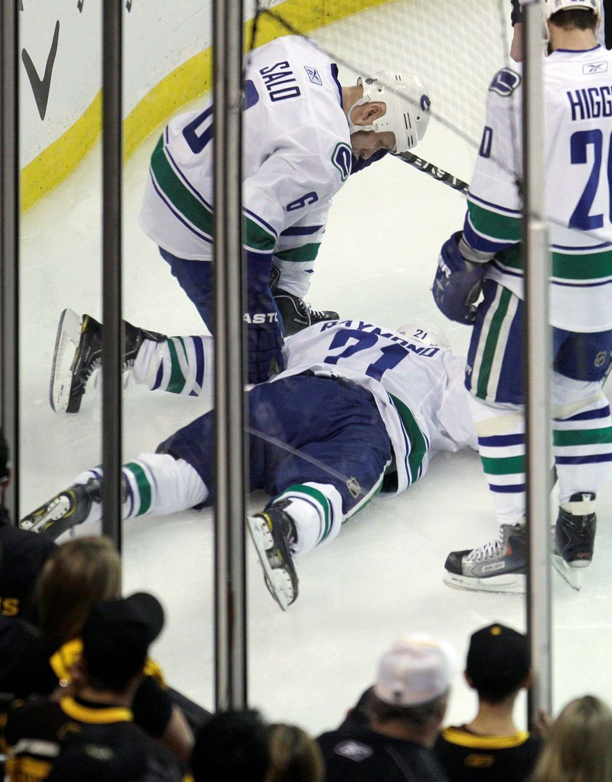 ASSOCIATED PRESS Vancouver forward Mason Raymond was left with a broken back after being checked into the boards by Boston defenseman Johnny Boychuk just 20 seconds into the first period of Game 6.