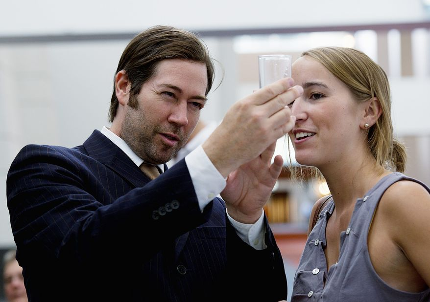 Nathan Ackerman of Washington seems to know what to look for in a good glass of water as he scrutinizes one of the 24 entrants in the water taste test at the Washington Convention Center.  (Barbara L. Salisbury/The Washington Times)