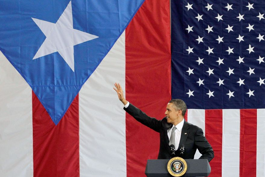 ASSOCIATED PRESS President Obama acknowledges the crowd gathered inside the Muniz Air National Guard Base hangar shortly after his arrival in San Juan, Puerto Rico, on Tuesday. His visit marked the first one by a sitting president since John F. Kennedy in 1961. The Puerto Rican flag provided half the backdrop for the podium.