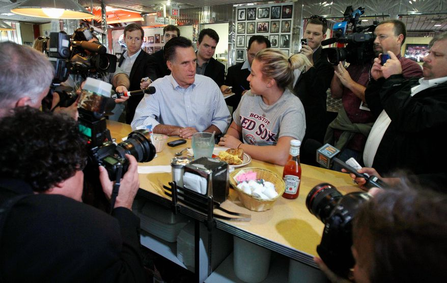 ASSOCIATED PRESS Former Massachusetts Gov. Mitt Romney, a Republican presidential hopeful, talks with a woman eating breakfast at the counter of a diner as they are surrounded by photographers and reporters during a campaign stop in Derry, N.H., on Tuesday. Many of the GOP candidates took advantage of campaigning in the state after Monday evening's Republican presidential debate.