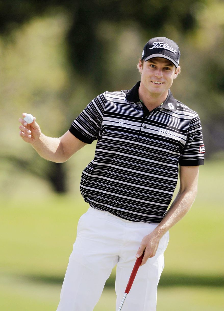 Nick Watney holds up his ball after an eagle putt on the first hole during the third round at the Cadillac Championship golf tournament in Doral, Fla., Saturday, March 12, 2011. (AP Photo/Lynne Sladky)