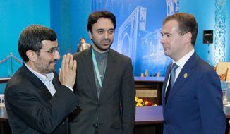Iranian President Mahmoud Ahmadinejad (left) and Russian President Dmitry Medvedev (right) meet on the sidelines of the summit of the Shanghai Cooperation Organization in Kazakhstan's capital, Astana, on Wednesday, June 15, 2011. The man in the middle was not identified. (AP Photo/RIA Novosti, Mikhail Klimentyev, Presidential Press Service)