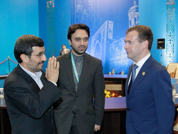Iranian President Mahmoud Ahmadinejad (left) and Russian President Dmitry Medvedev (right) meet on the sidelines of the summit of the Shanghai Cooperation Organization in Kazakhstan's capital, Astana, on Wednesday, June 15, 2011. The man in the middle was not identified. (AP Photo/RIA Novosti, Mikhail Klimentyev
