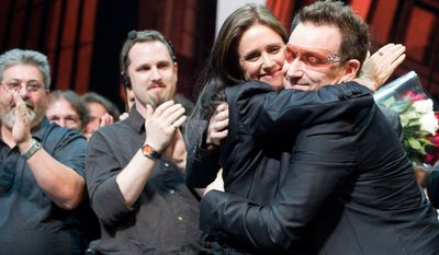 "Julie Taymor and Bono hug onstage during the curtain call of the opening-night performance of the Broadway musical ""Spider-Man: Turn Off the Dark"" in New York on Tuesday, June 14, 2011. (AP Photo/Charles Sykes)"